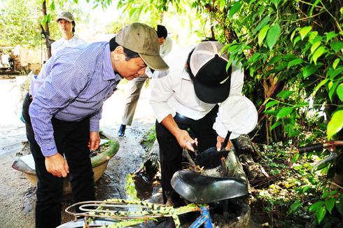 Kiểm tra lăng quăng trong các mũ, nón chứa nước tại vườn nhà người dân
