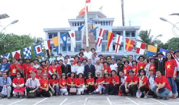 Đoàn kiều bào chụp ảnh lưu niệm bên cột mốc chủ quyền tại đảo Song Tử Tây