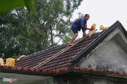 Người dân Hà Tĩnh gia cố mái nhà đề phòng tốc mái. Ảnh: Zingnews.