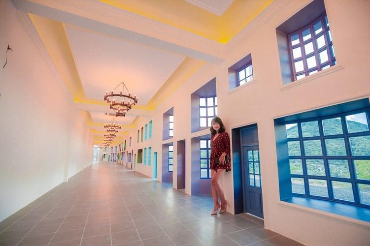 Bước vào bên trong các cánh cửa màu xanh lại là một không gian cực sang trọng với những dàn đèn chùm đơn giản nhưng mang phong cách cổ và dãy hành lang dài tạo độ sâu cho bức ảnh.