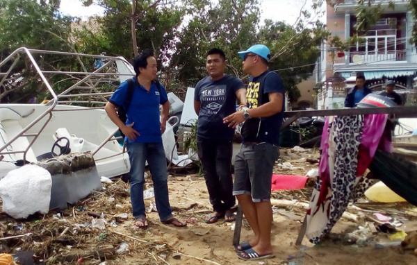 Anh Luân (ở giữa) trò chuyện cùng các nhà báo sau hành động lao ra biển cứu  người. (Ảnh: Dân trí)