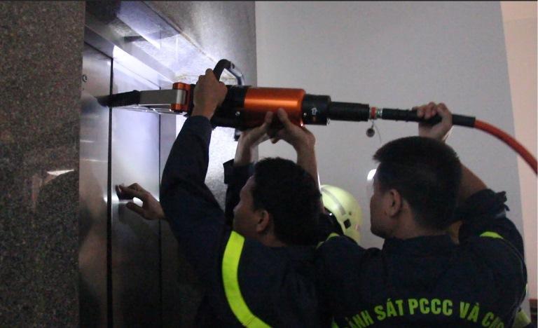 Các chiến sĩ dùng thiết bị banh thủy lực để mở cửa thang máy, đưa nạn nhân ra ngoài.