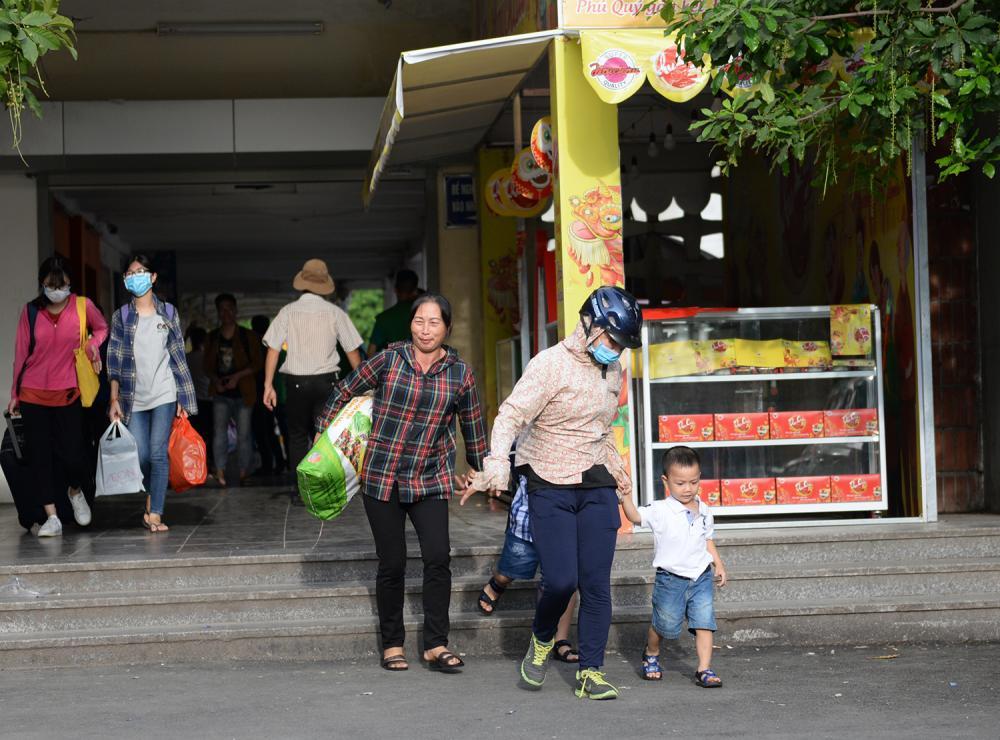 Bên trong sân chính của bến xe, nhiều gia đình hối hả để lên kịp chuyến xe.