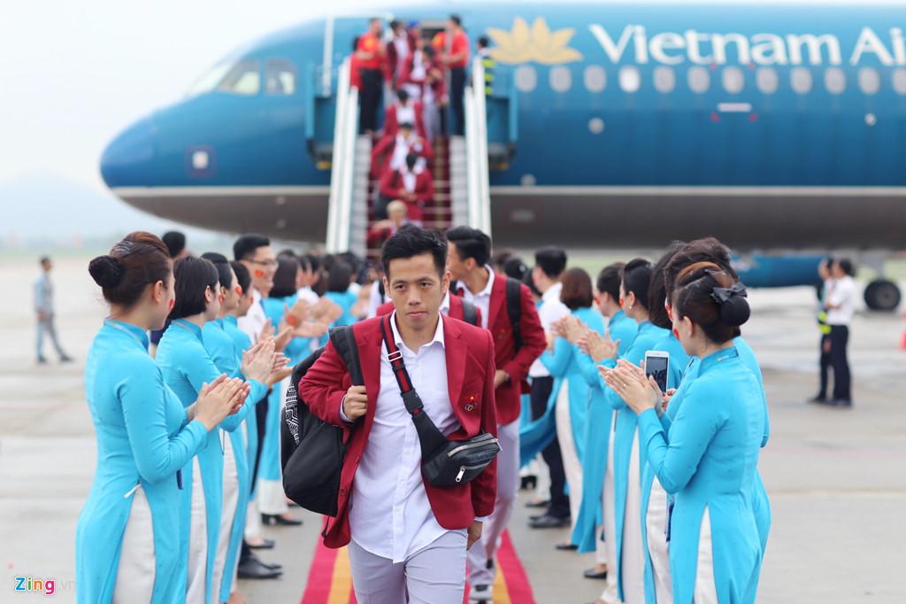 Máy bay hạ cánh xuống sân bay Nội Bài lúc 14h. Đội trưởng Văn Quyết dẫn đầu xuống cầu thang trong tâm trạng vui buồn lẫn lộn.