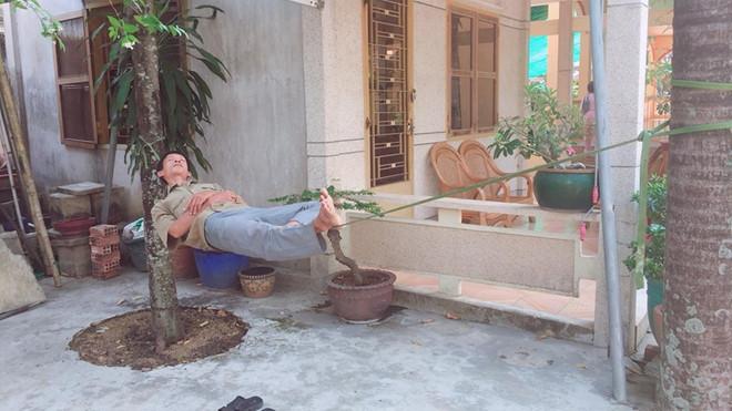 Người đàn ông trung niên nằm ngủ trưa ngon lành trên dây. Ảnh: Quốc Cường.