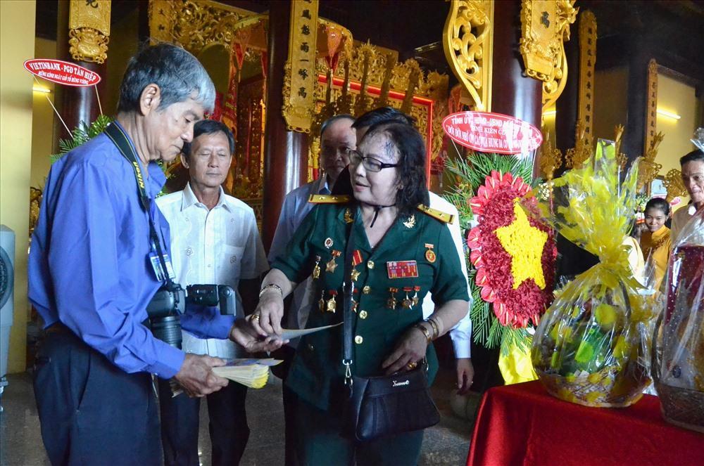 Ban tổ chức lễ hội thận trọng phát tờ rơi giới thiệu Đền Hùng Tân Hiệp để mọi người hiểu thêm về lịch sử hình thành và phát triển của di tích lâu đời này. (Ảnh: Luc Tùng)