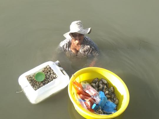 Cụ Rớt ngâm mình trong nước để mò nghêu, sò bán cho du khách