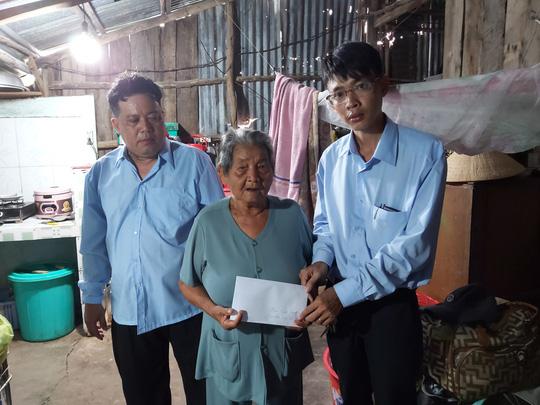 Đại diện Báo Người Lao Động cùng đại diện xã Hàm Ninh trao tiền hỗ trợ cho cụ Rớt