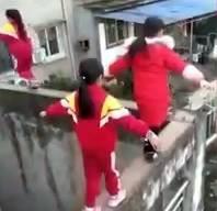 3 học sinh Trung Quốc bất chấp nguy hiểm khi đi trên bờ tường hẹp, cao 20 m. Ảnh cắt từ clip.