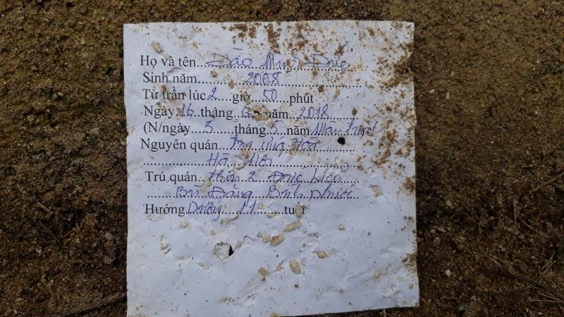 Người dân ghi lại tên của nạn nhân sau khi thắp nhang tại vị trí cháu bé xấu số qua đời