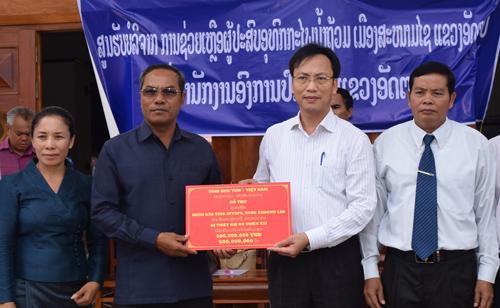 Đoàn công tác tỉnh Kon Tum trao 500 triệu đồng hỗ trợ người dân tỉnh Attapeu khắc phục hậu quả sự cố đập thủy điện. Ảnh: Bạch Dương