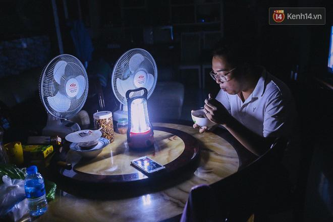 Ăn cơm trong ánh sáng le lói. Do điều kiện chưa cho phép, cả gia đình cư dân này chỉ có một chiếc đèn dùng để ăn cơm.