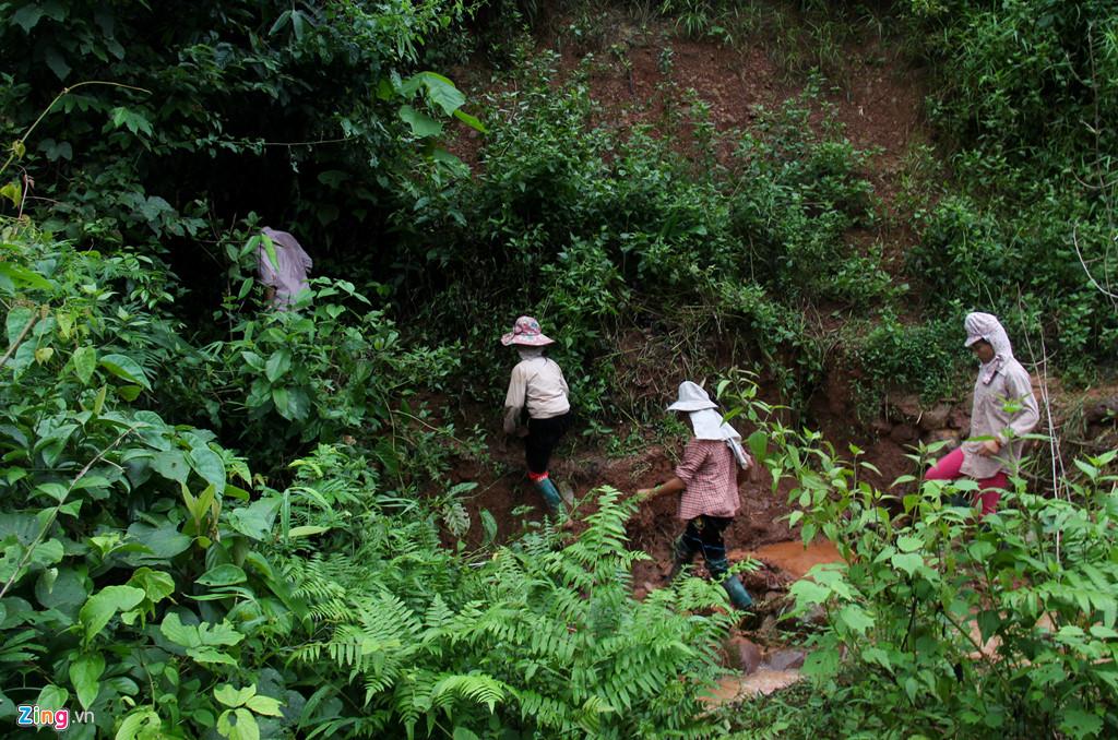Để đi đến điểm sạt lở, người thân và lực lượng chức năng phải đi bộ hơn 2 km đường rừng trơn trượt.