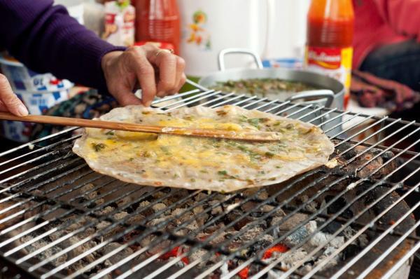Người nướng phải thật khéo tay để quết trứng đều hết bánh tráng. (Nguồn: Firewaterw)