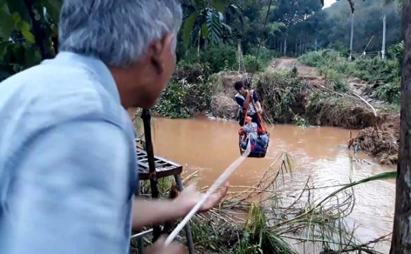 Những học sinh phải có người lớn kéo qua suối. Ảnh: Tuấn Kiệt.