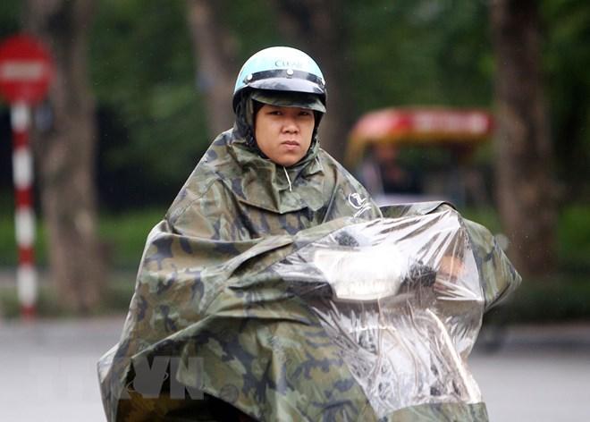 Người tham gia giao thông chống chọi với mưa rét trên đường Đinh Tiên Hoàng (Hà Nội). (Ảnh: Danh Lam/TTXVN)