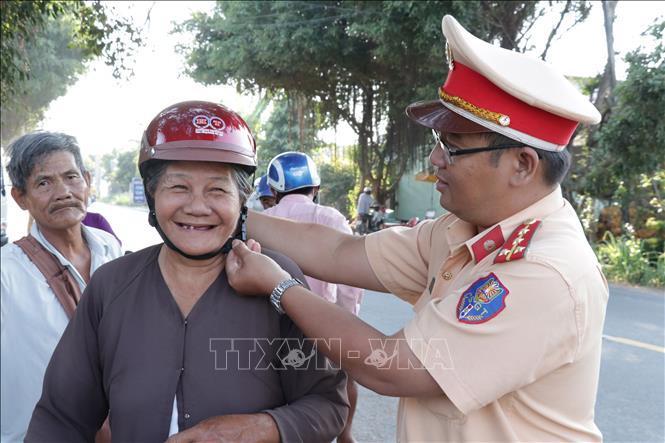 Các chiến sĩ cảnh sát giao thông tặng nón bảo hiểm đúng quy chuẩn cho người dân.