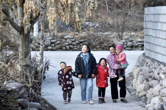 Bamu cùng các con mình đi trên con đường mới sửa. Ảnh: Tân Hoa Xã