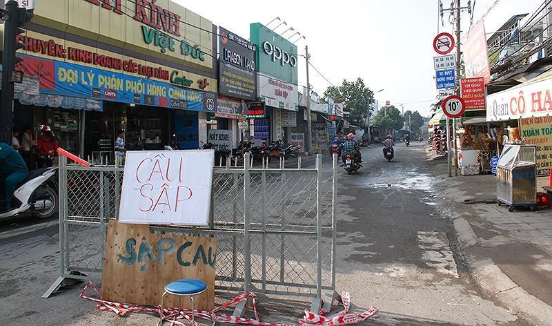 Ở hai đầu cầu trên đường Lê Văn Lương, lực lượng chức năng dựng biển cảnh báo để tổ chức lại giao thông. Các phương tiện muốn đi qua phải chọn lộ trình khác qua đường Nguyễn Bình hoặc đường Đào Sư Tích.