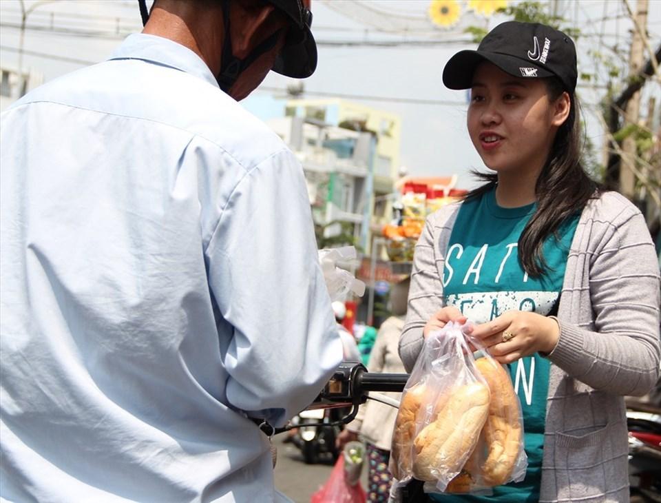 Người dân phát ba'ŋh mì cho du khách đi lễ.