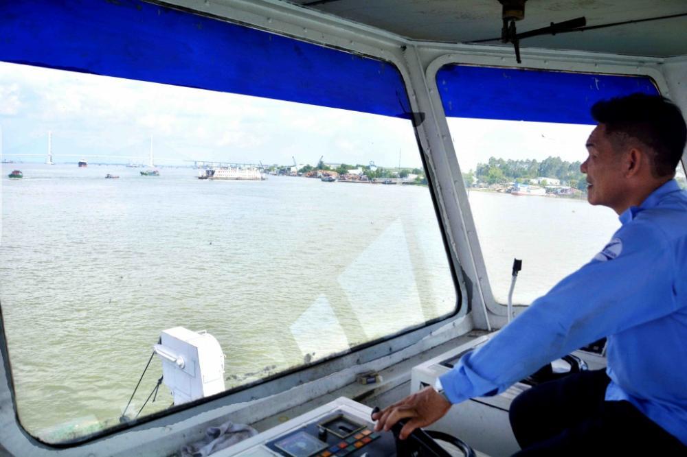 Thuyền trường đang điều khiển một chuyến phà băng qua sông Hậu