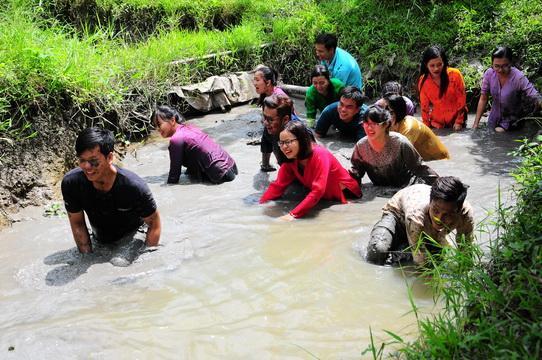 Du khách hóa thân thành nông dân trãi nghiệm tát mương bắt cá tại Khu du lịch sinh thái Lung Cột Cầu.
