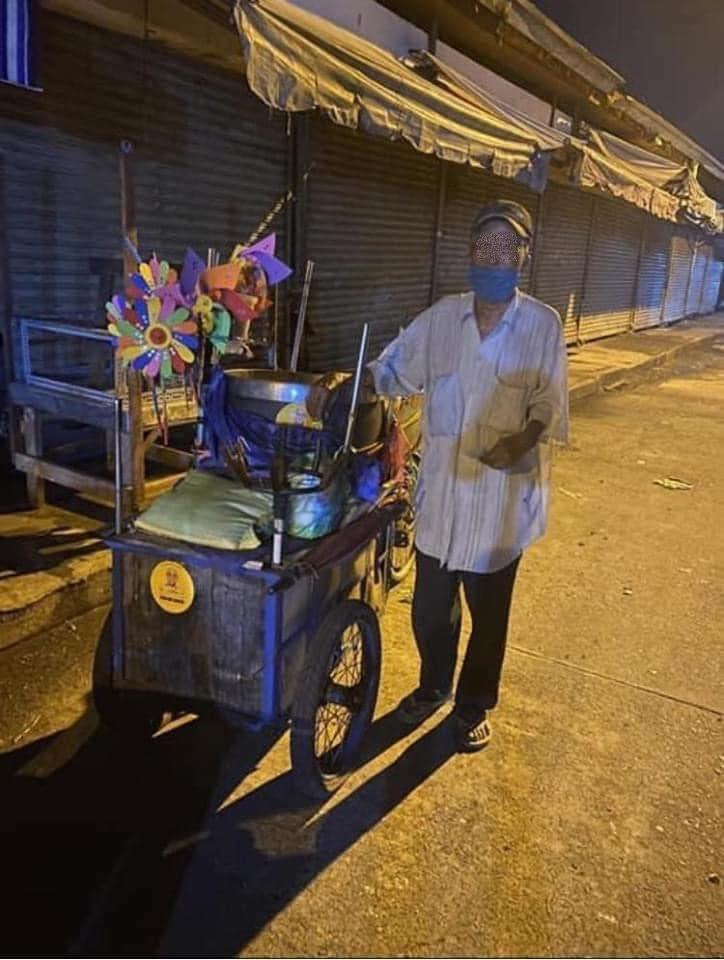 Cụ ông bán chong chóng bị đánh tráo tiền trong đêm tối. (Ảnh: FB M.T.)
