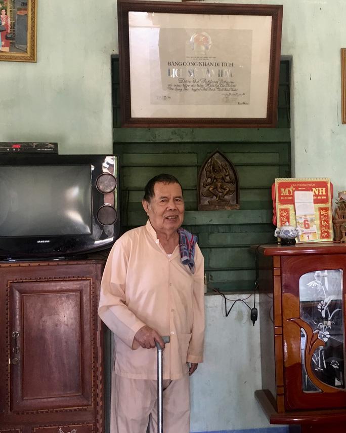 Ông Lư Thái Thuổi bên tấm bằng công nhận di tích lịch sử - văn hóa cấp quốc gia được công nhận năm 1993.