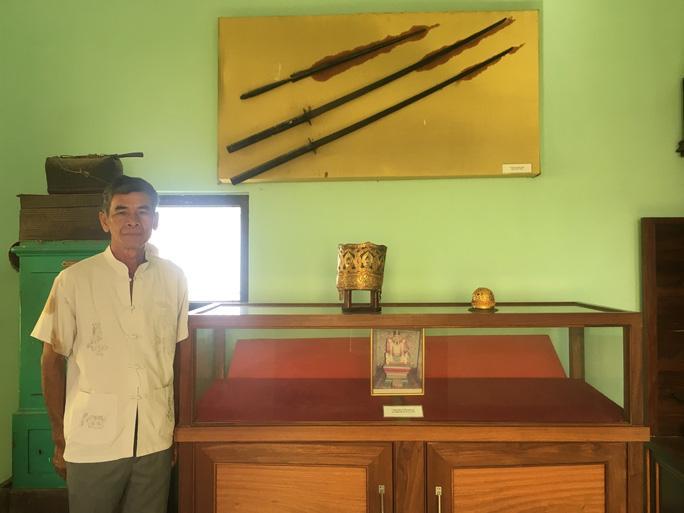 Ông Văn Hồng Tịnh bên kho báu của hoàng tộc và bức ảnh chụp tượng vua Pô Klong Mơhnai.
