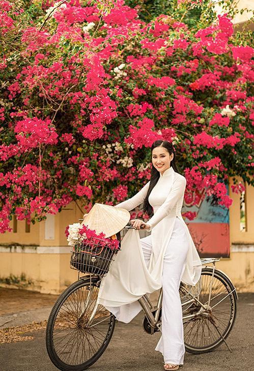 Đoàn Hồng Trang diện áo dài trắng đạp xe dạo phố khi về thăm quê. Mùa này những giàn hoa giấy đang nở rộ rực rỡ ở nhiều góc đường.