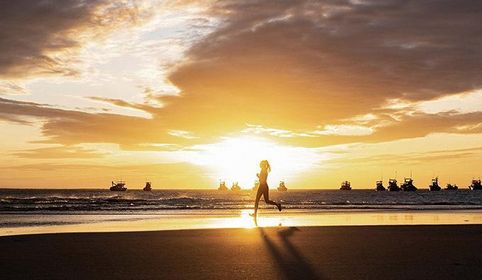 Hồng Trang chạy bộ trên bãi biển lúc hừng đông.