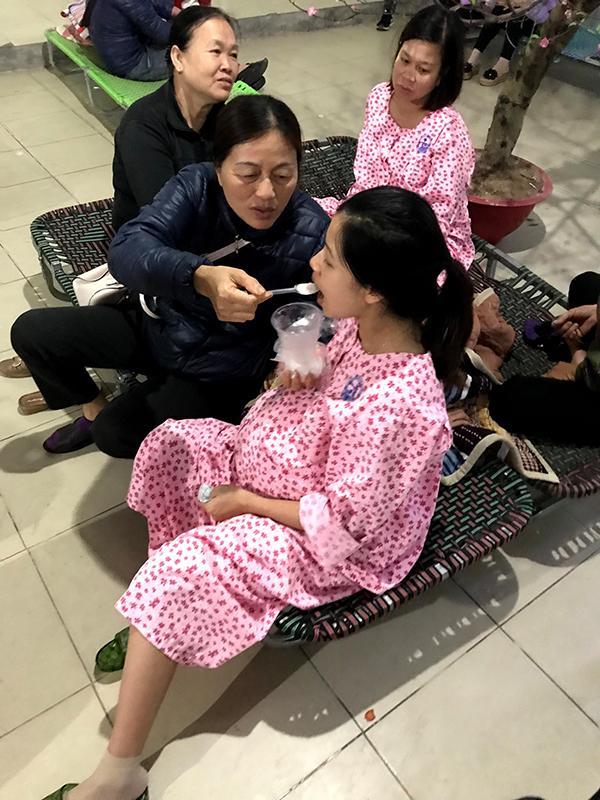 Mẹ chồng bón cháo cho con dâu ăn trong bệnh viện chờ sinh đẻ.