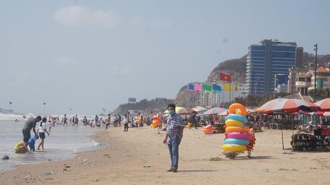 Dưới bãi biển người dân, du khách đi dạo mang khẩu trang kín bít.