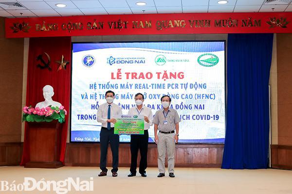 Đại diện Công ty cổ phần đầu tư kinh doanh Golf Long Thành trao bảng tượng trưng tài trợ 4 máy oxy dòng cao (HFNC). Ảnh: Thế Đông