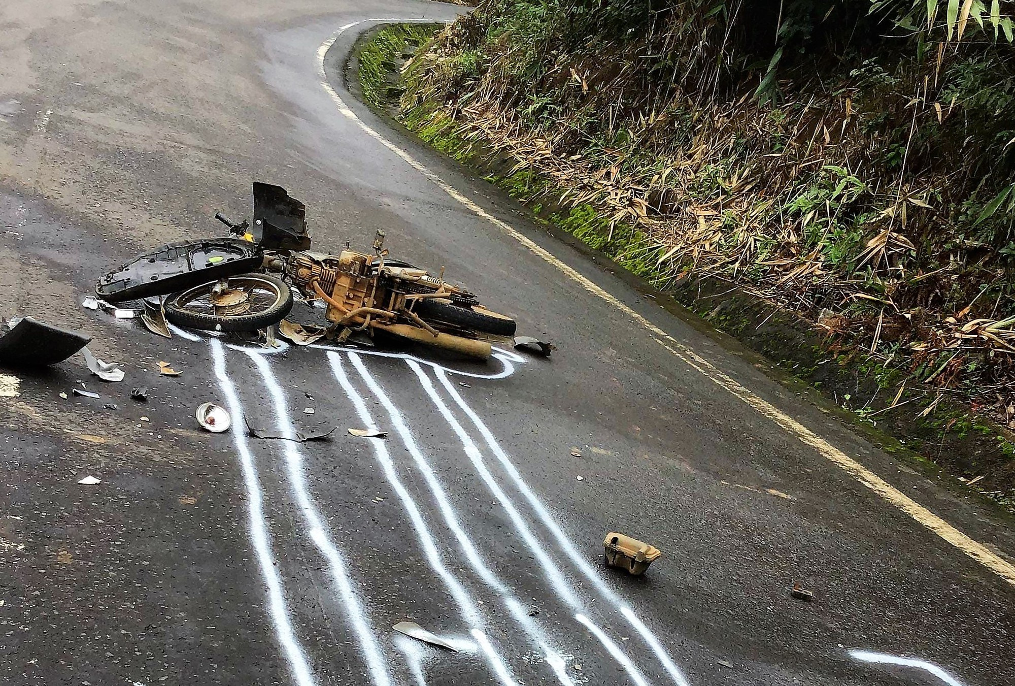 Chiếc xe máy bị hất văng xa, hư hỏng nặng.