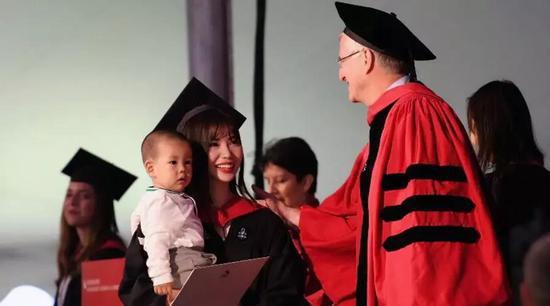 Lỗ Lâm Hi bước lên bục nhận bằng thạc sĩ tại Havard, trên tay bế theo con nhỏ một cách đầy tự hào