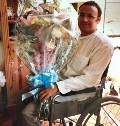 Paul Zetter ngồi xe lăn khi đang hồi phục ở Anh, cầm bó hoa Hội đồng Anh tặng, cách đây gần 20 năm. Ảnh: Nhân vật cung cấp