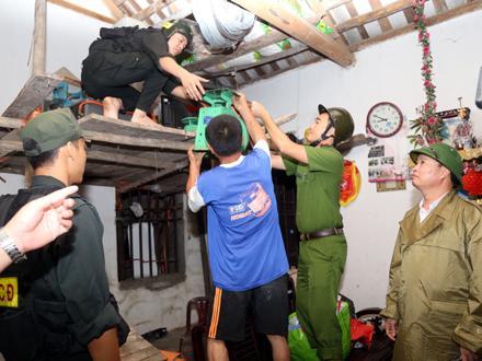 Lực lượng Công an giúp nhân dân di chuyển tài sản đến nơi an toàn. Ảnh: Đức Lam