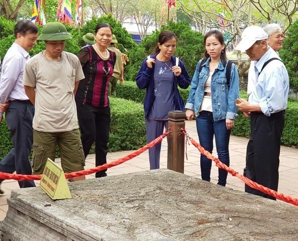 Du khách tham quan Long sàng - báu vật quốc gia tại Khu di tích Cố đô Hoa Lư. Ảnh: NT