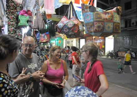 Khách du lịch nước ngoài hào hứng với các sản phẩm thủ công mỹ nghệ.