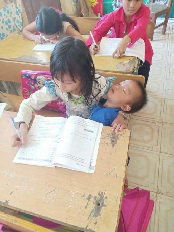 Cô bé vừa bế em vừa học bài.
