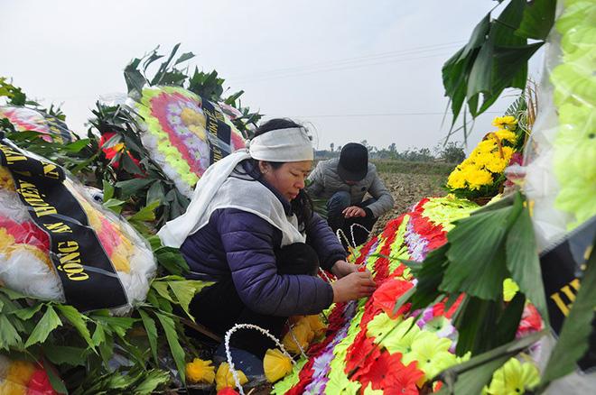 Những bông hoa được gỡ từ vòng hoa ra cắm lên các nấm mộ