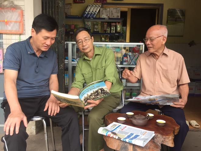 Ông Dương Quang Lựa (ở giữa) chia sẻ cùng bạn bè, đồng đội về những năm tháng chiến đấu. Ảnh: NVCC