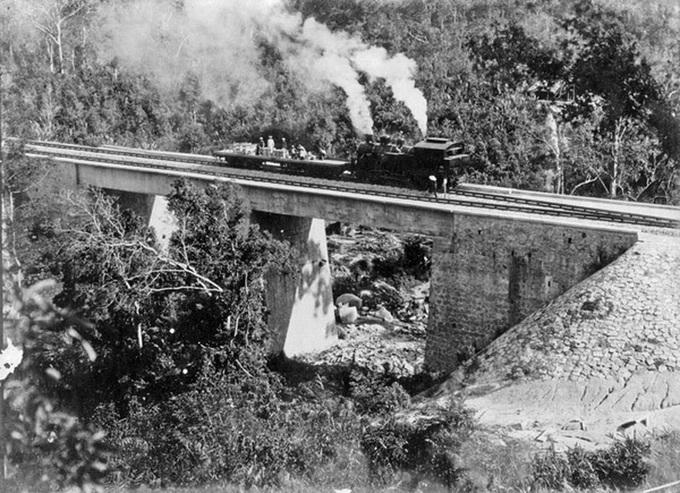 Tuyến tàu lửa Đà Lạt - Tháp Chàm được thi công năm 1908 nối tỉnh Lâm Đồng và Ninh Thuận. Sau 24 năm xây dựng, toàn tuyến dài 84 km hoàn thành và đưa vào hoạt động. Trong ảnh là tàu hỏa chạy trên cầu bắc qua vực sâu trên đèo Ngoạn Mục năm 1930. Ảnh: Tư liệu