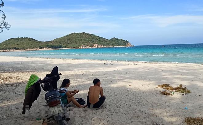 Người dân buồn rầu nhìn bãi biển Bình Tiên. (Ảnh: Hùng Võ/Vietnam+)
