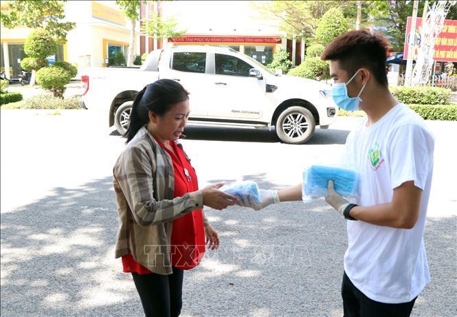 Các tình nguyện viên cấp phát miễn phí khẩu trang cho người dân trên địa bàn thành phố Phan Rang-Tháp Chàm. Ảnh: Công Thử/TTXVN