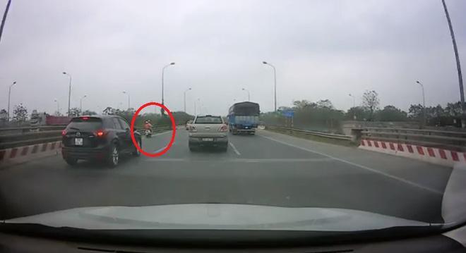Người phụ nữ đi xe máy lạc trên cao tốc. (Ảnh cắt từ clip)