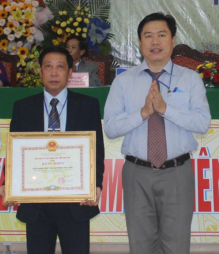 Phó Chủ tịch UBND tỉnh Trần Hữu Thế trao bằng khen cho Liên minh HTX tỉnh về những đóng góp của đơn vị này trong thời gian qua - Ảnh: MINH DUYÊN
