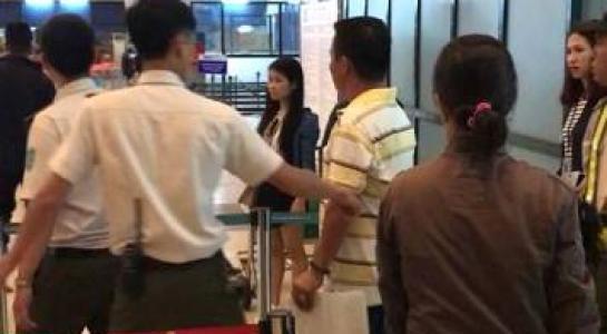 Ông Trần Chiến Thắng mặc áo sọc ngang, tay cầm giấy chửi bới an ninh sân bay