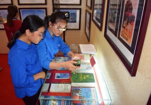 Một em học sinh chụp lại tư liệu trong triển lãm